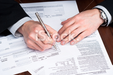 stock-photo-13692063-men-filling-out-documents-on-a-desk.jpg