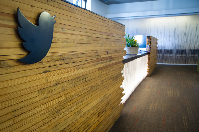A wooden wall with a black Twitter logo on it