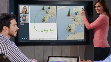 Surface Hub on a wall being used with a touch pen
