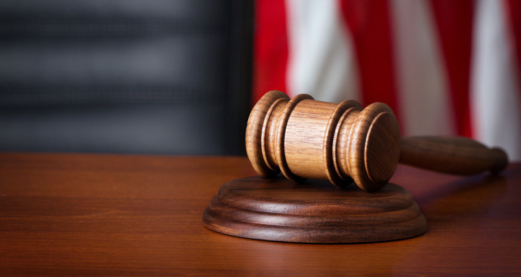 A gavel resting on a table with a blurred US flag in the background