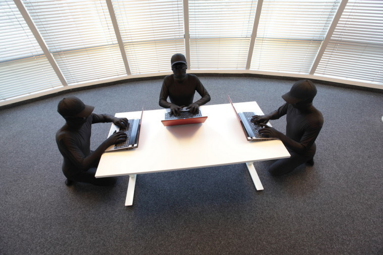 A group of 3 hackers sitting around a desk with laptops in front of them
