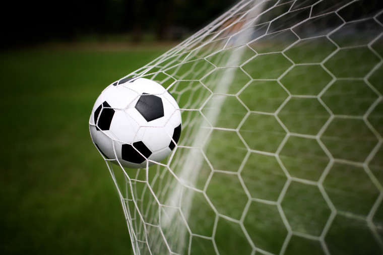 A football hiting the back of the net.