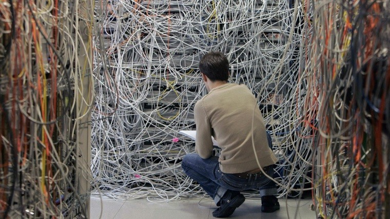 man crouching at a server rack