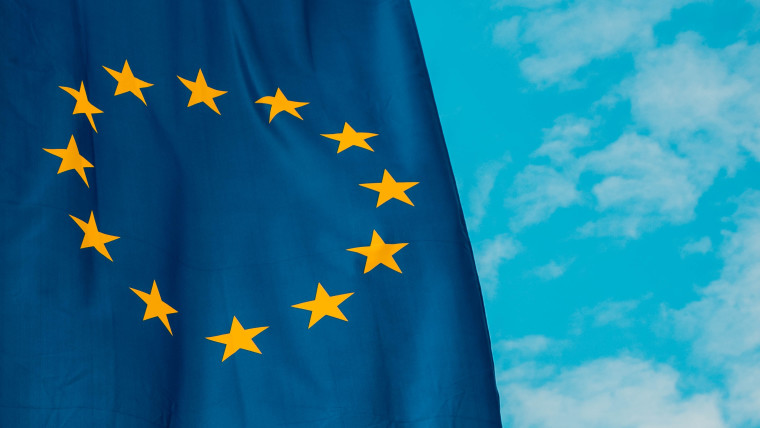The EU flag with a blue sky in the background