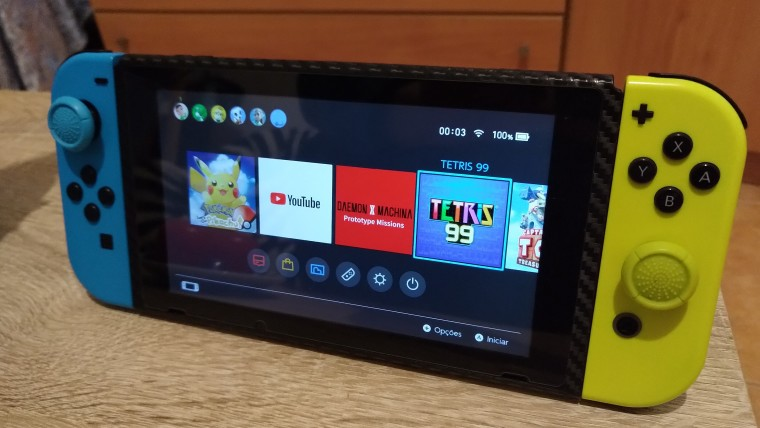 A Nintendo Switch with blue and yellow Joy-Con attached standing on a wooden table