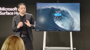 Panos Panay standing in front of the Surface Hub 2S