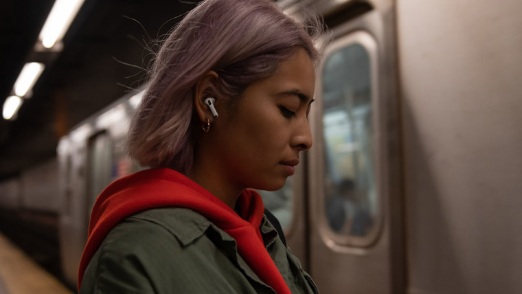 Woman wearing AirPods Pro and standing next to a train