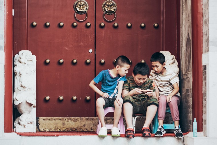 Children sitting at a doorstep looking at a phone screen