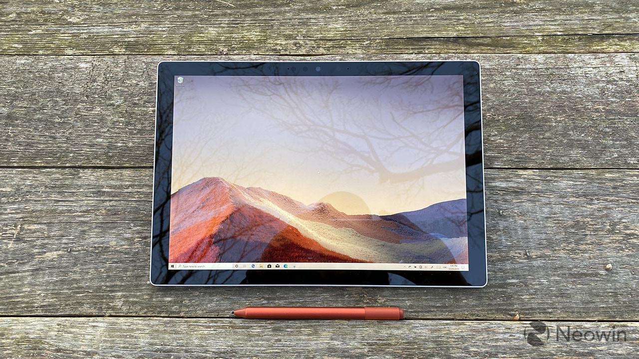 Surface Pro 7+ tablet on wooden table with red Surface Pen