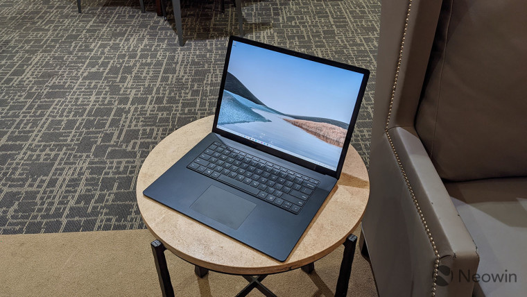 Surface Laptop 3 on a round table next to a couch
