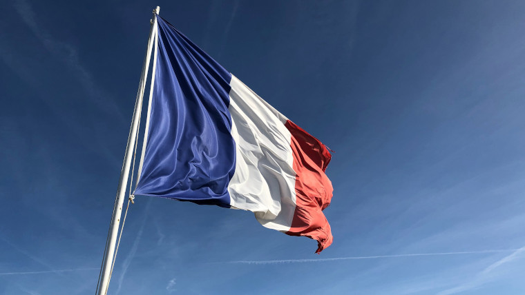 The French flag with the blue sky in the background