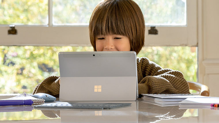 Back of a Surface Go 2 standing on a table and being used by a child