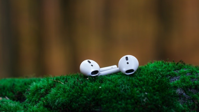 Apple AirPods on a green surface