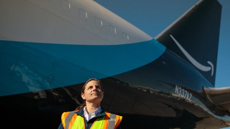 Amazon worker in front of an Amazon Air plane