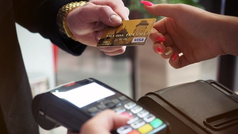 A person handing over a bank card to pay for shopping