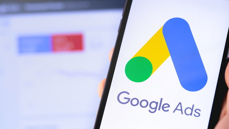 A hand holding a phone showing the Google Ads logo on the screen