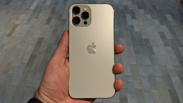 iPhone 12 Pro Max in the left hand with grey flooring in the background