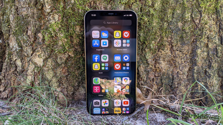 An iPhone 12 Pro Max standing upright on the ground leaning against a tree trunk