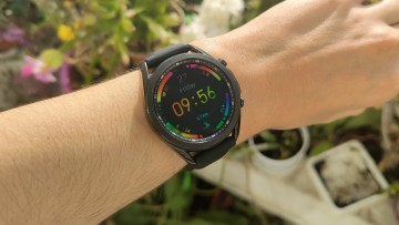 Samsung Galaxy Watch3 on a wrist displaying a colorful watch face