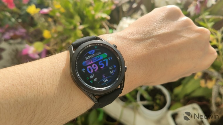 A Samsung Galaxy Watch on a wrist displaying a colorful watch face