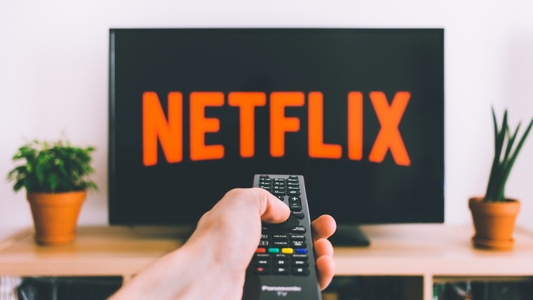 A person pointing their remote at a TV displaying the Netflix logo