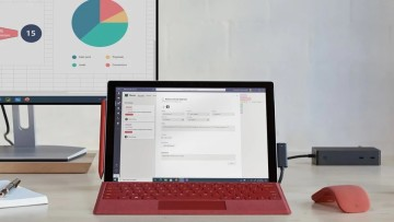 Surface Pro 7+ with red keyboard and red mouse in front of monitor