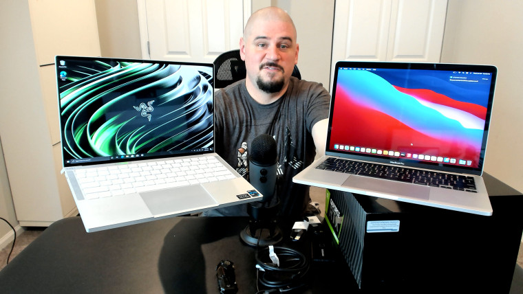 Bald idiot holding a Razer Book 13 and a MacBook Pro 13