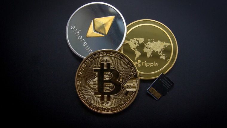 Bitcoin, Ethereum and Ripple coins and SD card on grey background