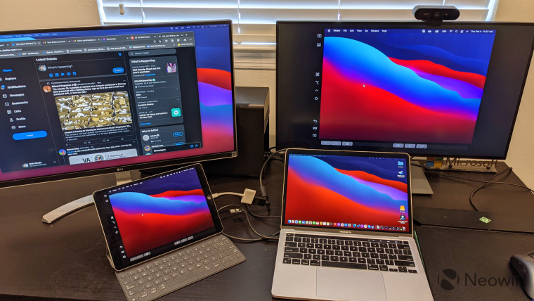 MacBook Pro and iPad Pro connected to two monitors