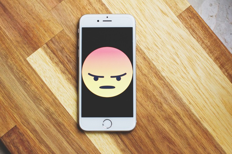 An iPhone on a wooden table with an angry emoji on the screen