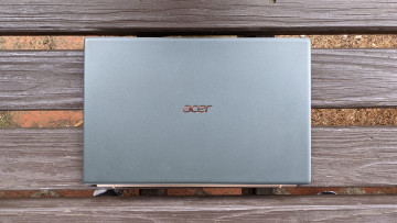 Green and gold Acer Swift 5 closed on wooden background