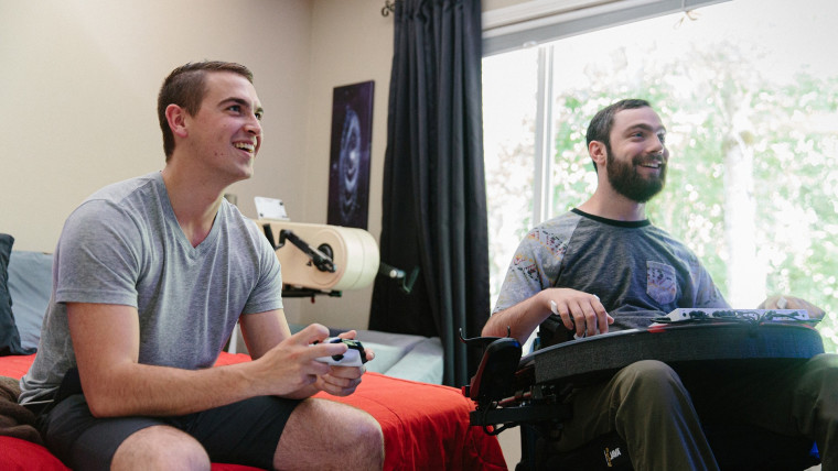 Two people playing games, one using Xbox controller and the other using Accessibility controller