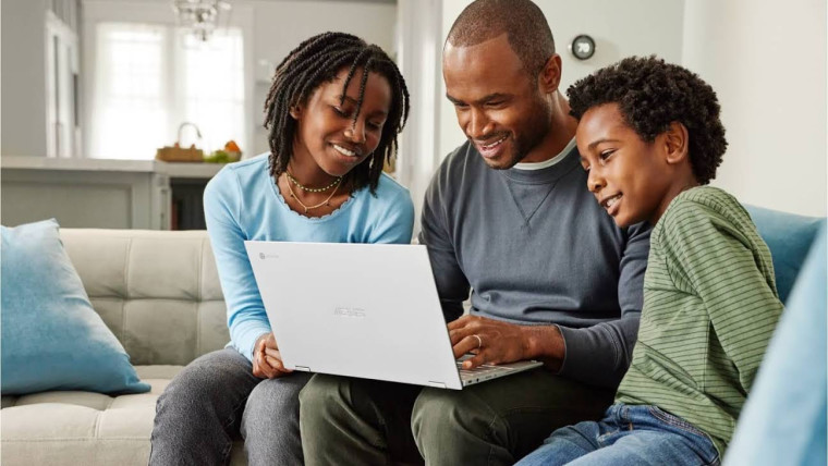 Three people sitting on a sofa and looking at an ASUS Chromebook being held by the man in the middle