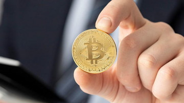 Person holding a Bitcoin coin