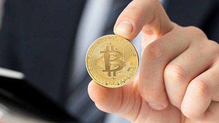 Person holding a Bitcoin coin