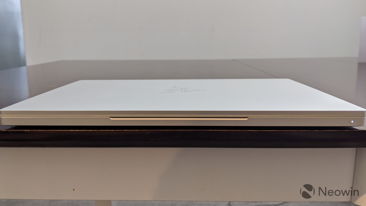 Front view of closed Razer Book 13 on wooden table