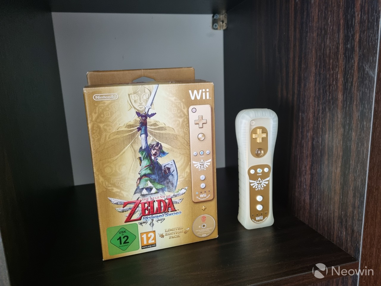 A video game box next to a Wii Remote