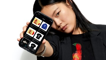 A woman holding a phone showing the Amazon Music merch shop for Billie Eilish