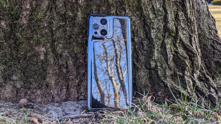 OPPO Find X3 Pro leaning up against tree trunk