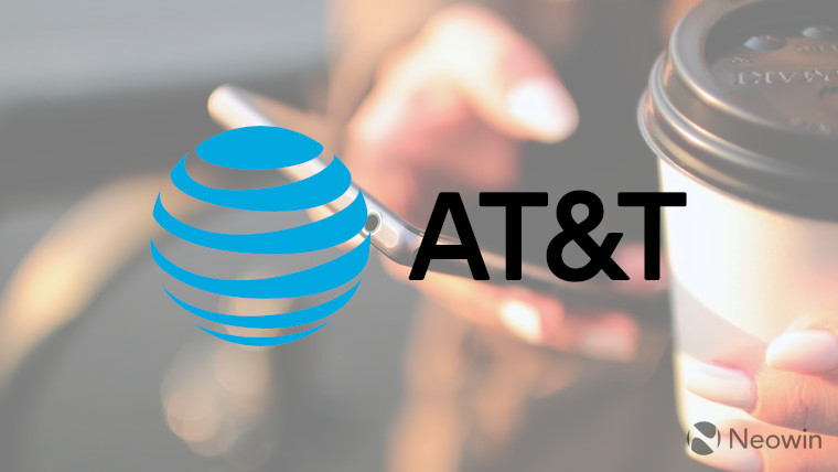 The AT&T logo in front of a person holding a phone and coffee