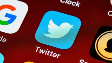 A zoomed in phone screen with the Twitter app logo prominent in the center