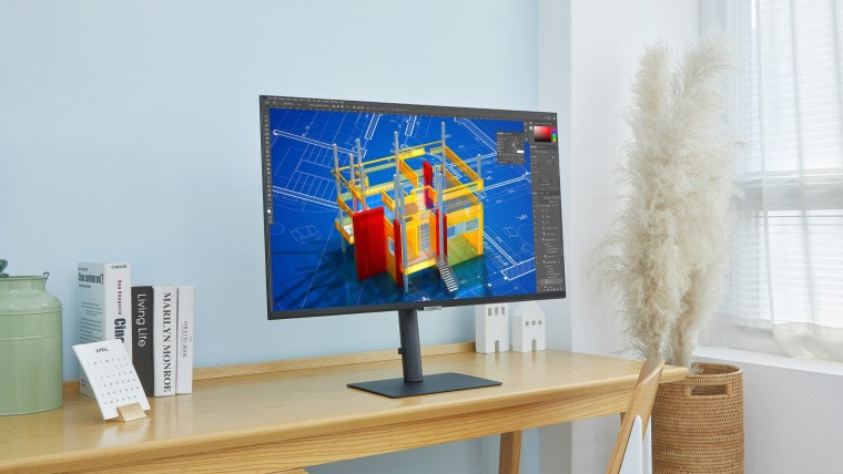 A flat Samsung monitor on a wooden desk