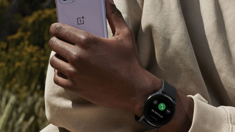Someone wearing OnePlus Watch and holding OnePlus 9