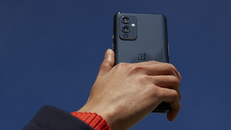 OnePlus 9 in Astral Black being held in the air