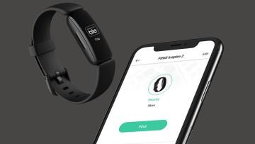 A smartphone screen showing the Tile app alongside a Fitbit Inspire 2 wearable