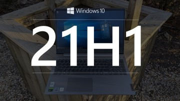 Windows 10 21H1 text with a Windows laptop in the background