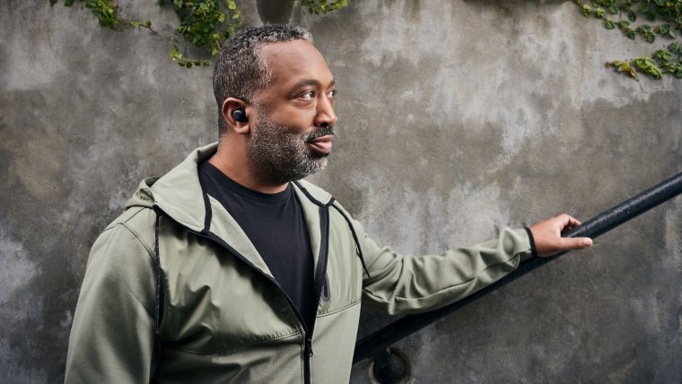 A man wearing Amazon&039s all-new Echo Buds in his ear