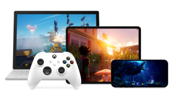 An Xbox controller next to a smartphone tablet and laptop all running different games