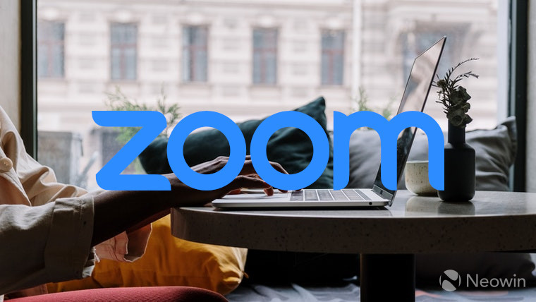 The Zoom logo with a laptop in the background
