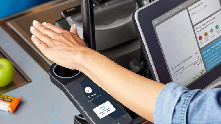 An Amazon customer is using the contactless payment service Amazon One which scans the palm